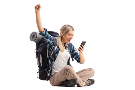 Cheerful female hiker sitting on the ground and looking at a mobile phone isolated on white background Standard-Bild