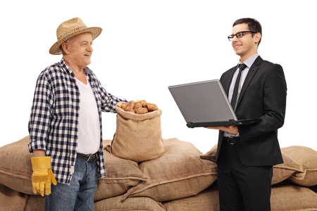 sackful: Farmer and a businessman with a laptop in front of a pile of burlap sacks with potatoes isolated on white background