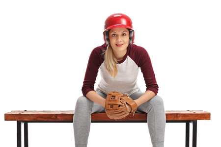 player bench: Female baseball player with a catcher glove and a helmet sitting on a bench isolated on white background