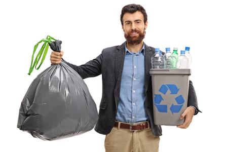 Tirante barbuto che tiene una borsa di immondizia e un recipiente di riciclaggio in pieno di bottiglie di plastica isolate su fondo bianco