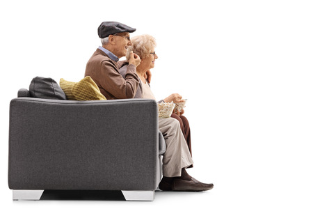 eating popcorn: Elderly man and woman sitting on a sofa and eating popcorn isolated on white background Stock Photo