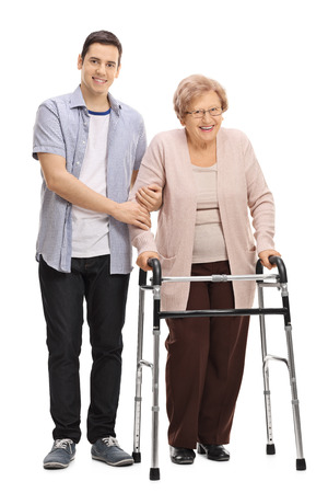 Full length portrait of a young man helping a mature woman with a walker isolated on white background