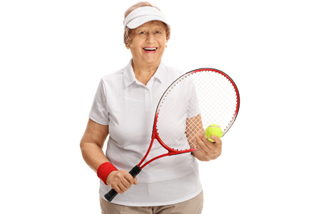 70s tennis: Joyful senior tennis player holding a racket and a tennis ball isolated on white background