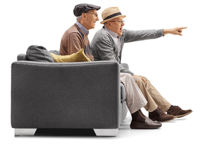 them: Two mature men sitting on a couch with one of them pointing isolated on white background Stock Photo
