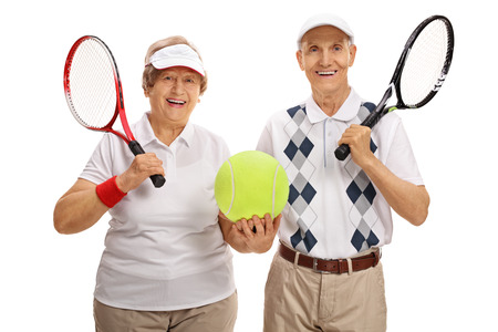 70s tennis: Happy elderly tennis players holding a big tennis ball isolated on white background Stock Photo