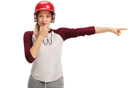entrenador de béisbol de las mujeres que sopla un silbato y apuntando hacia la derecha aislada en el fondo blanco Foto de archivo