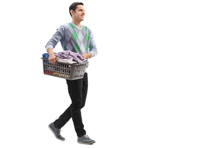 Full length portrait of a guy carrying a laundry basket isolated on white background