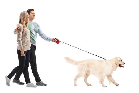 Retrato de cuerpo entero de una joven pareja feliz que recorre un perro aislado en el fondo blanco