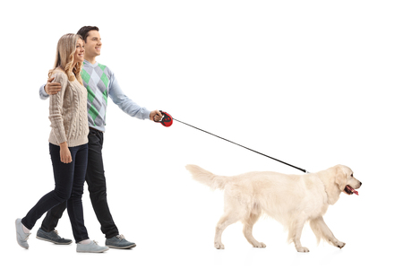 Full length portrait of a happy young couple walking a dog isolated on white background