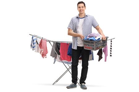 In voller Länge Porträt eines glücklichen jungen Mann mit einem Wäschekorb vor einem Kleiderständer Trockner isoliert auf weißem Hintergrund