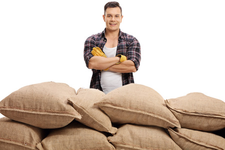sackful: Farmer posing with his arms crossed behind a pile of burlap sacks isolated on white background