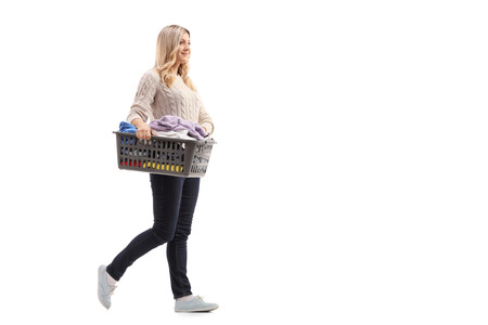 Full length portrait of a young woman carrying a laundry basket full of clothes isolated on white background