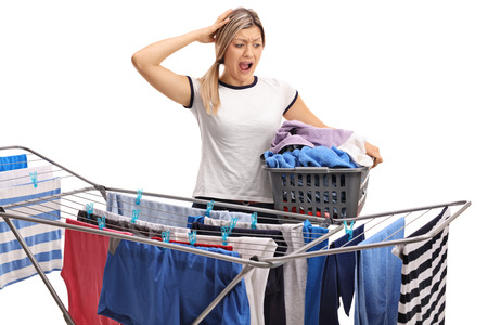 disbelief: Woman with a laundry basket holding her head in disbelief and looking at a clothing rack dryer isolated on white background Stock Photo