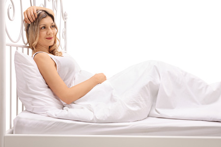 resting: Young woman lying in bed isolated on white background