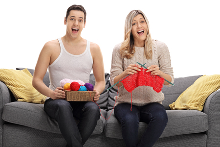 overjoyed: Overjoyed man wearing an undershirt sitting on a sofa and knitting with a woman isolated on white background
