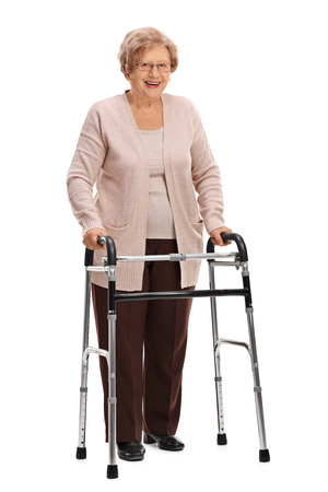 Full length portrait of a joyful mature woman with a walker isolated on white background