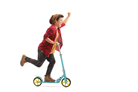 Full length portrait of an excited little boy riding a scooter and gesturing with his hand isolated on white background
