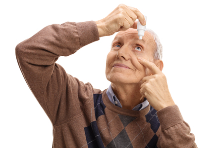 Mature man applying eye drops isolated on white background
