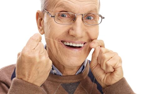 Hombre maduro uso de hilo dental sus dientes aislados sobre fondo blanco Foto de archivo