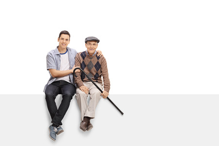 Young man and a senior sitting on a panel together isolated on white background