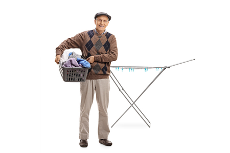 Full length portrait of a senior holding a laundry basket full of clothes in front of a clothing rack dryer isolated on white background Stock Photo