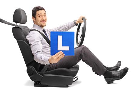 cinturon seguridad: Individuo que se sienta en un asiento de coche y la celebración de un L-signo aislado sobre fondo blanco
