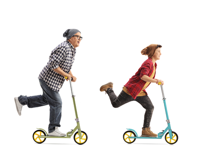 Full length portrait of a mature hipster and a boy riding scooters isolated on white background