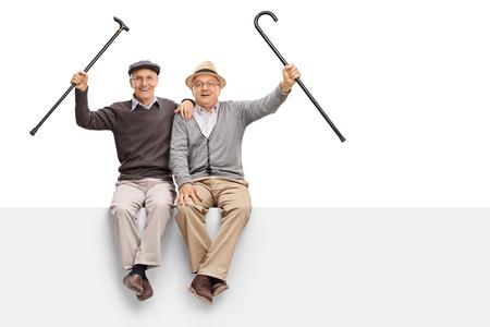 white: Joyful seniors with walking canes sitting on a panel isolated on white background Stock Photo