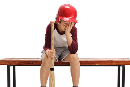 Sad kid with a baseball bat and a helmet sitting on a bench and holding his head in disbelief isolated on white background