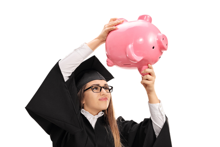Worried graduate student shaking a piggybank isolated on white background