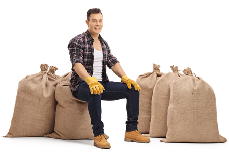 sackful: Happy farmer sitting on burlap sacks and looking at the camera isolated on white background