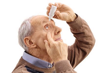 Bejaarde man de toepassing van oogdruppels op een witte achtergrond Stockfoto