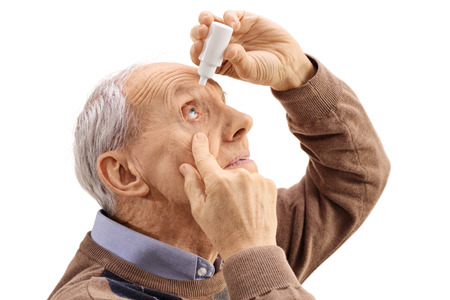 Elderly man applying eye drops isolated on white background