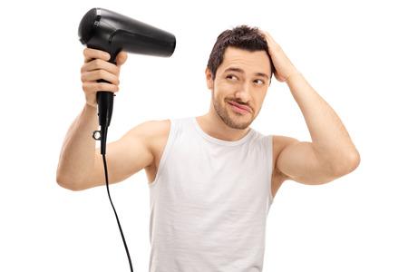 ハンサムな男打撃彼の髪は、白い背景で隔離の乾燥 写真素材