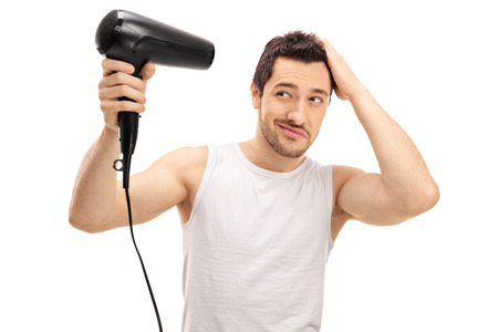 secador de pelo: El individuo hermoso golpe secado el pelo aislado en el fondo blanco Foto de archivo