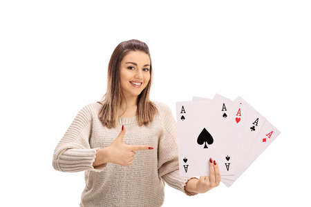 Joyful young woman holding four aces and pointing isolated on white background Stock Photo