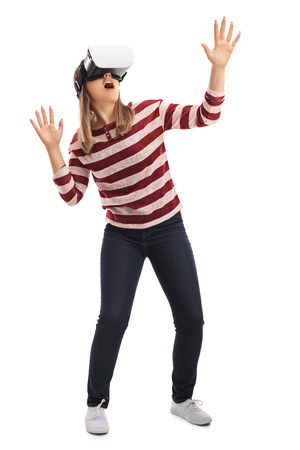 Full length portrait of a girl experiencing virtual reality through a VR headset isolated on white background Stock Photo