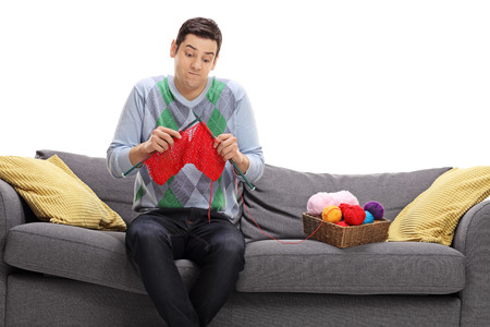 attempting: Confused guy sitting on a sofa and attempting to knit isolated on white background