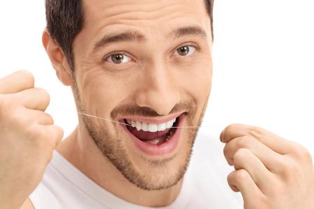 viso uomo: L'uomo flossing i denti isolato su sfondo bianco Archivio Fotografico