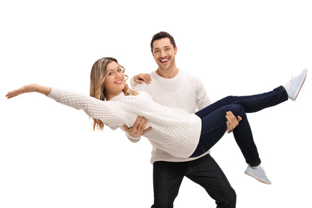 Happy young man carrying a young woman in his arms isolated on white background Stock Photo