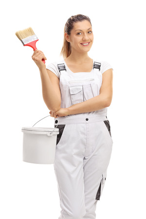 dungarees: Happy female decorator holding a paintbrush and a color bucket isolated on white background Stock Photo