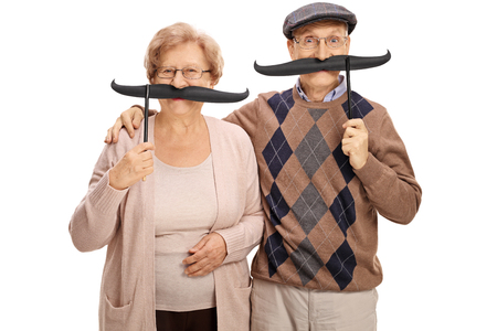 Cheerful seniors with big fake moustaches isolated on white background