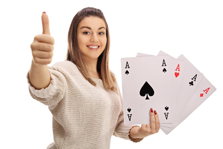 Happy girl giving a thumb up and holding four aces isolated on white background