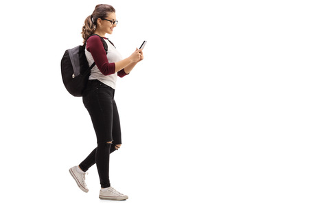 Full length profile shot of a female student walking and looking at a mobile phone isolated on white background