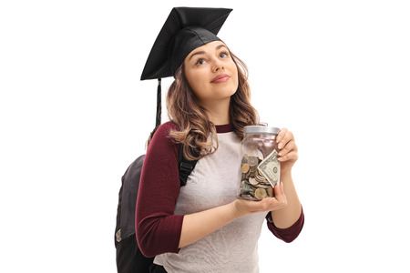 Female graduate student holding a jar filled with money and looking up isolated on white background Foto de archivo