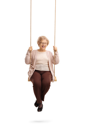 Happy elderly woman on a swing isolated on white background Stock Photo