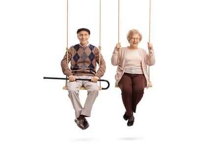 Elderly man and an elderly woman sitting on swings isolated on white background Standard-Bild