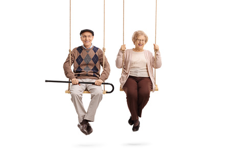 Elderly man and an elderly woman sitting on swings isolated on white background 스톡 콘텐츠