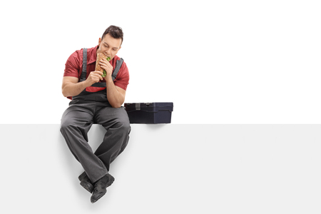 Worker sitting on a panel and eating a sandwich isolated on white background