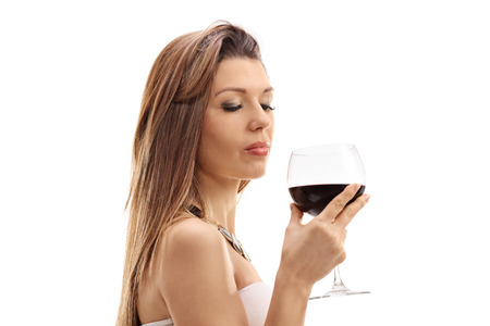 degustating: Young woman holding a glass of wine isolated on white background